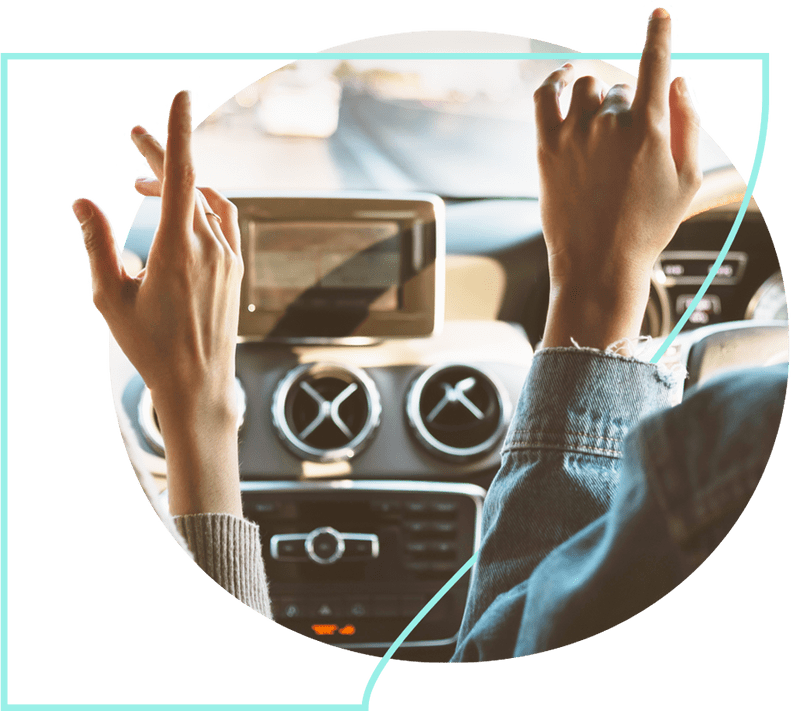 Two people in a car with their fingers up to the music from the radio